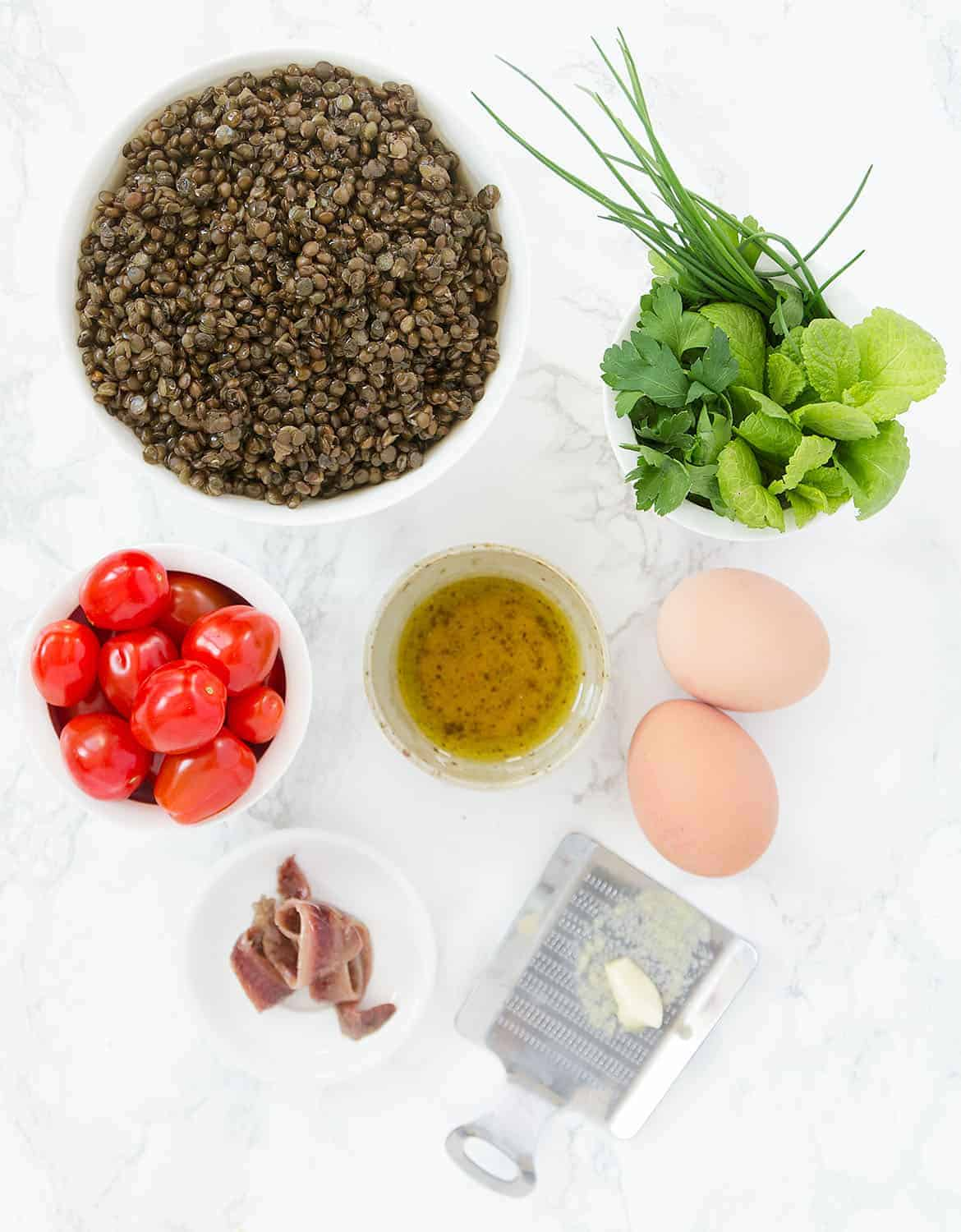 The ingredients for this puy lentil salad are arranged over a white background.