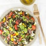 Mediterranean puy lentil salad with fresh herbs and cherry tomatoes over a grey plate, a fork and a small bowl with dressing in the background.