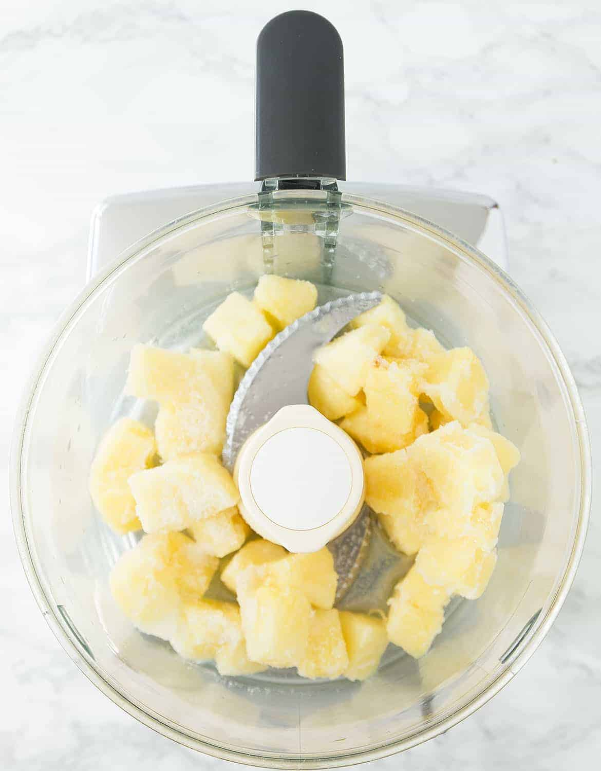 A food processor bowl with frozen pineapple chunks.