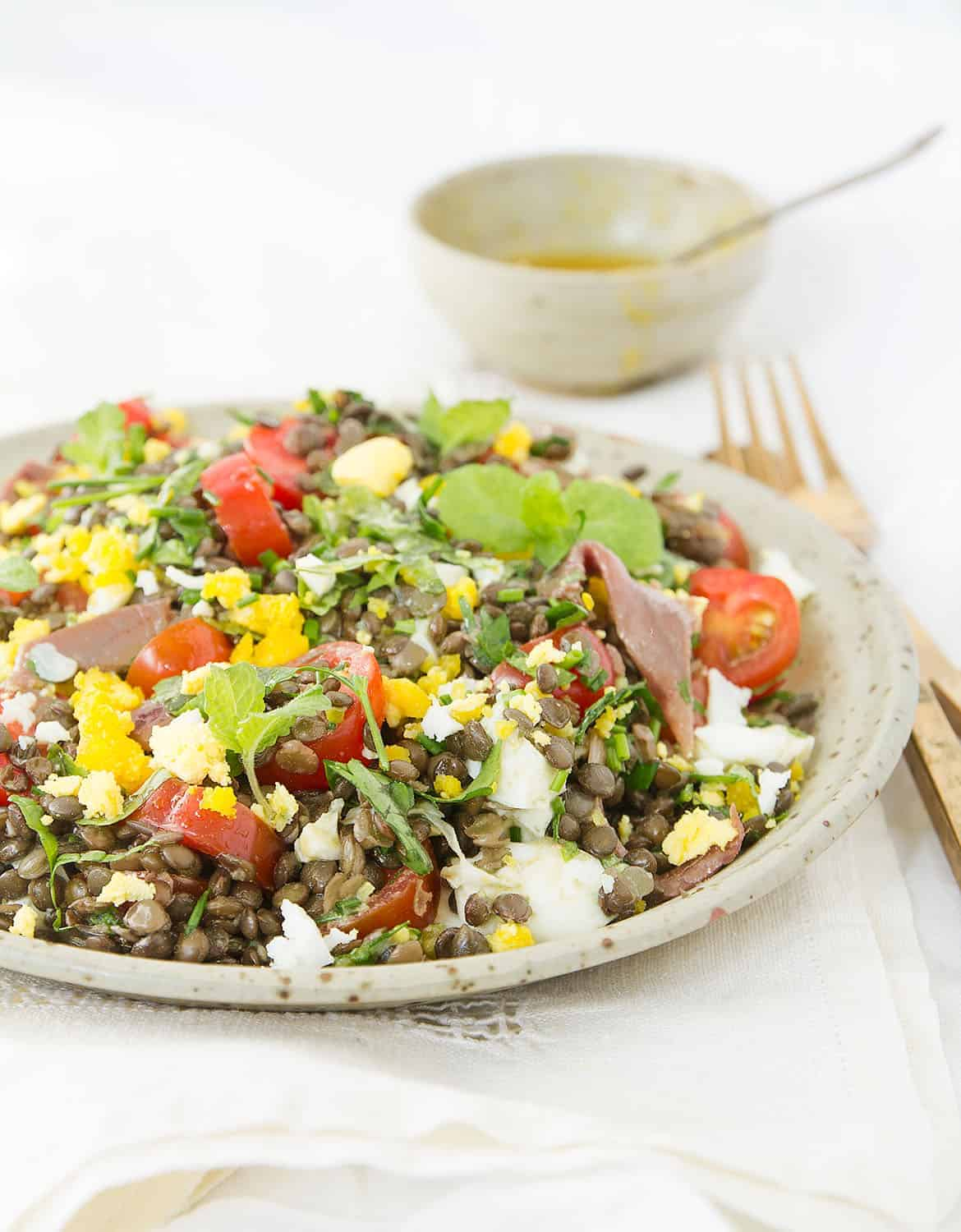 Mediterranean puy lentil salad with herbs and cherry tomatoes on a grey plate, a bowl with the dressing in the background.