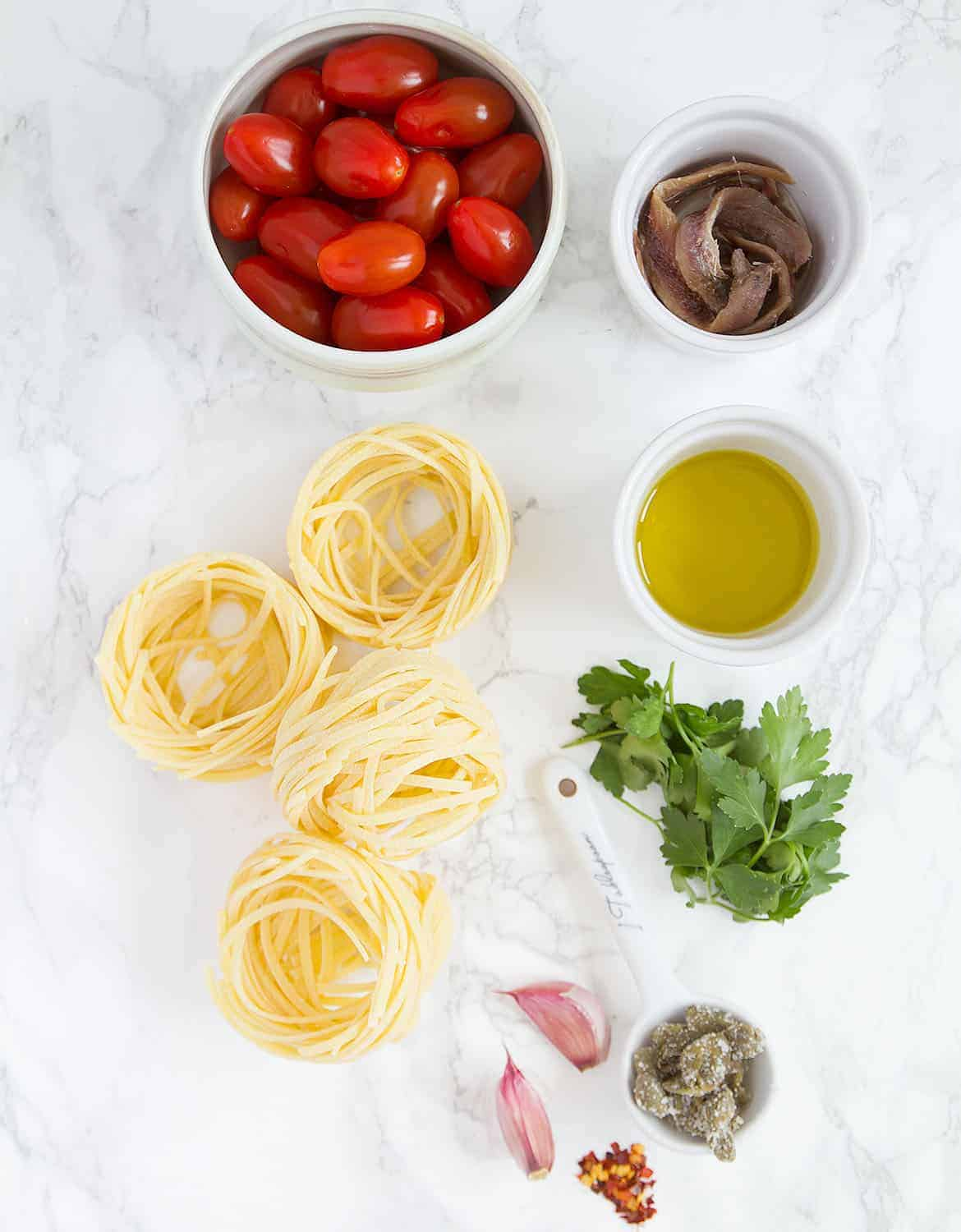 The ingredients for spaghetti alla puttanesca are arranged over a white table.