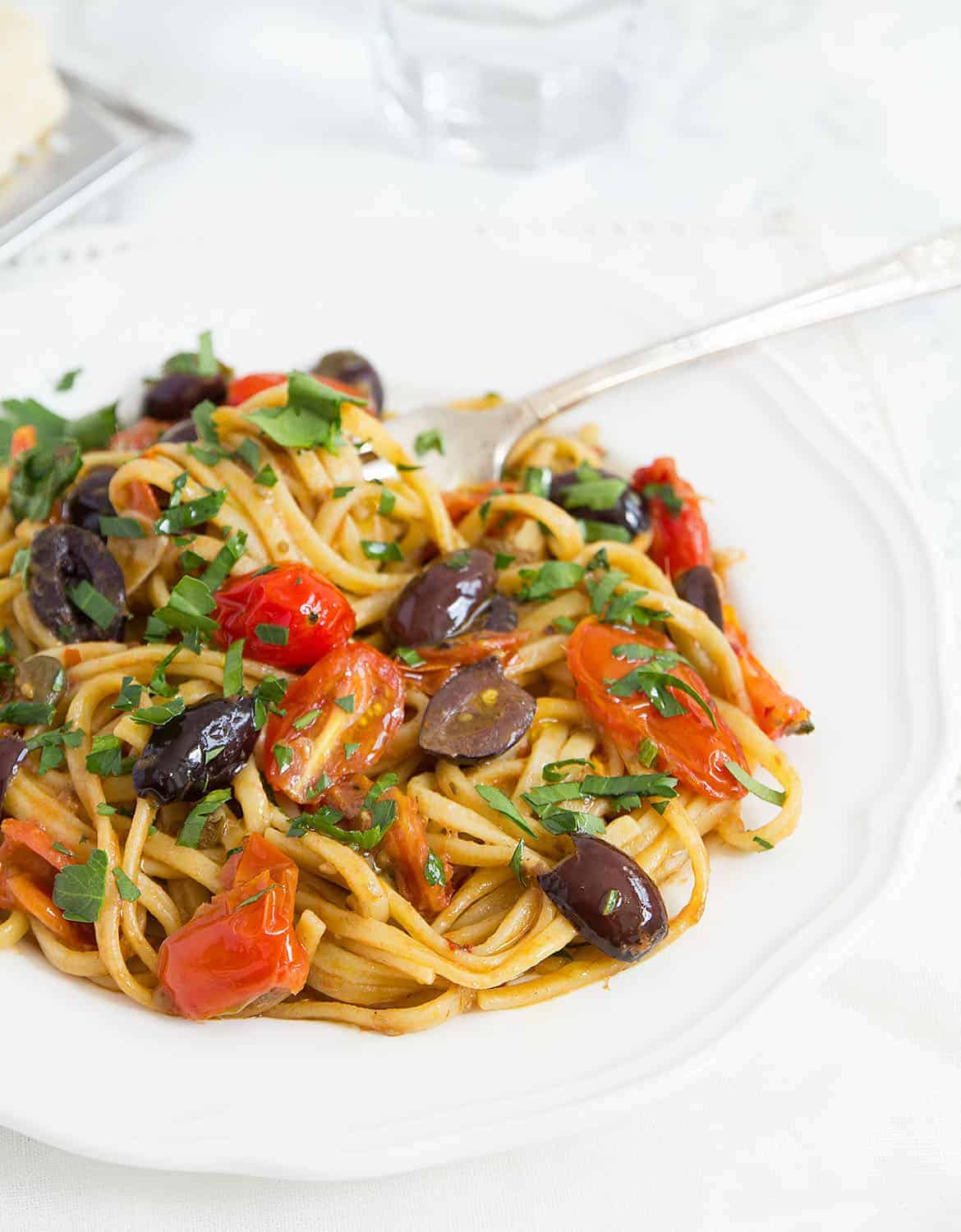 Spaghetti alla puttanesca with black olive and tomatoes on a white plate over a white background.