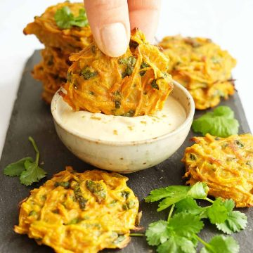 A hand dipping one of some carrot fritters into hummus dip.