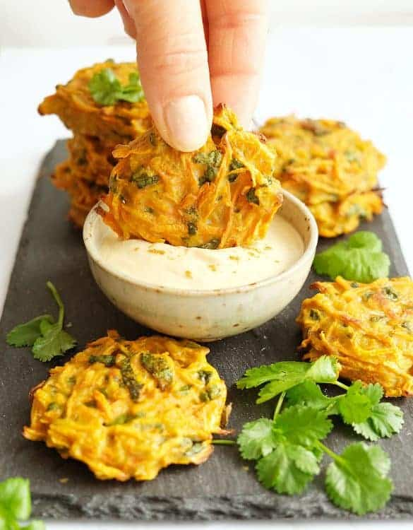 A hand is dipping one of some carrot fritters into hummus dip.