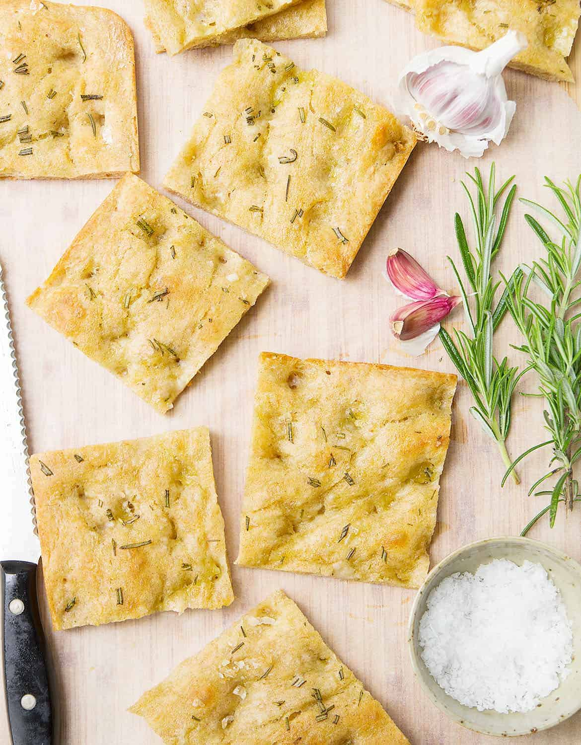 Slices of Italian focaccia on a chopping board with rosemary sprigs and garlic cloves.