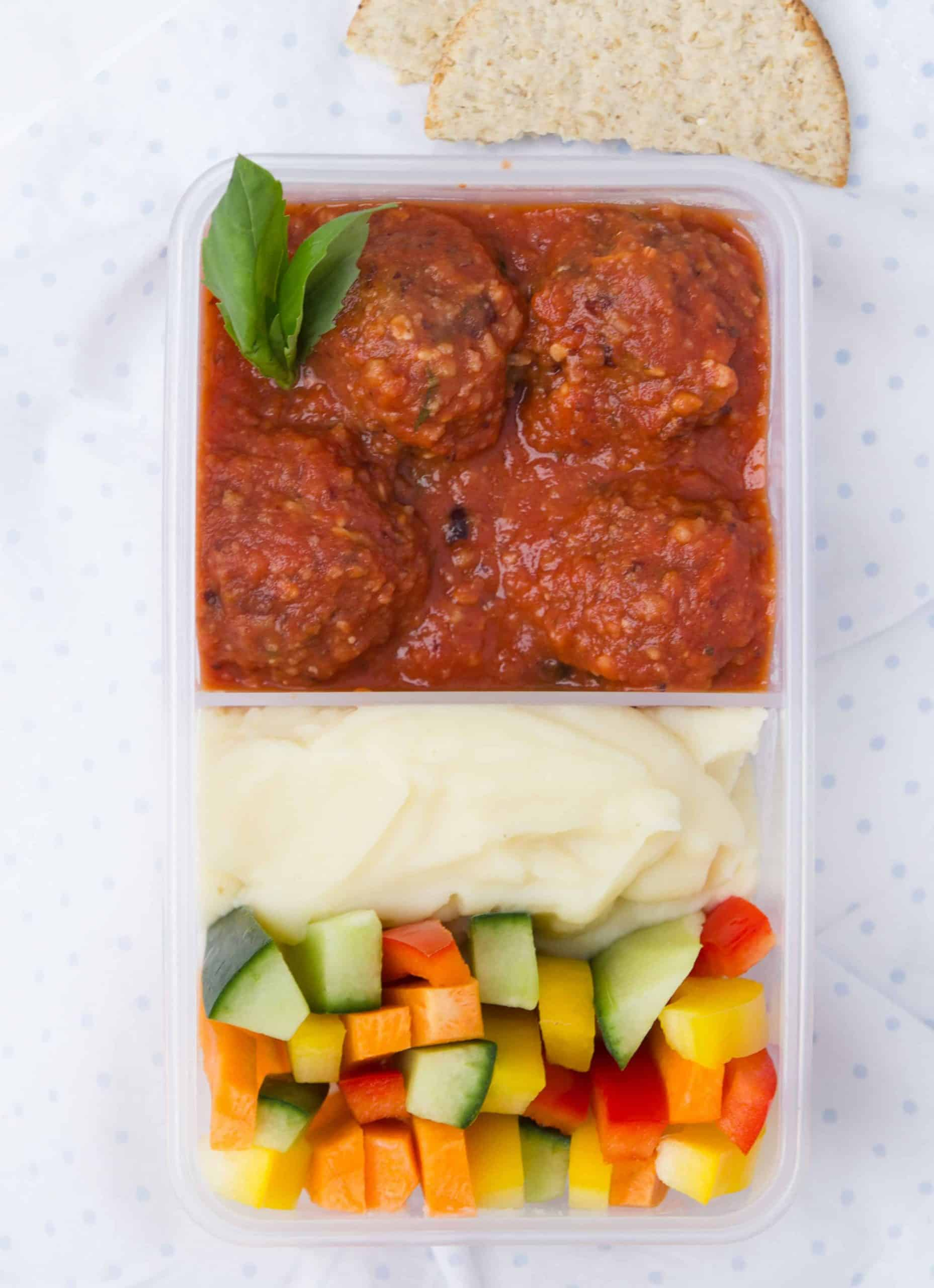 Vegan meatballs in tomato sauce in a meal prep container with veggie batons and mashed potatoes - The clever meal.