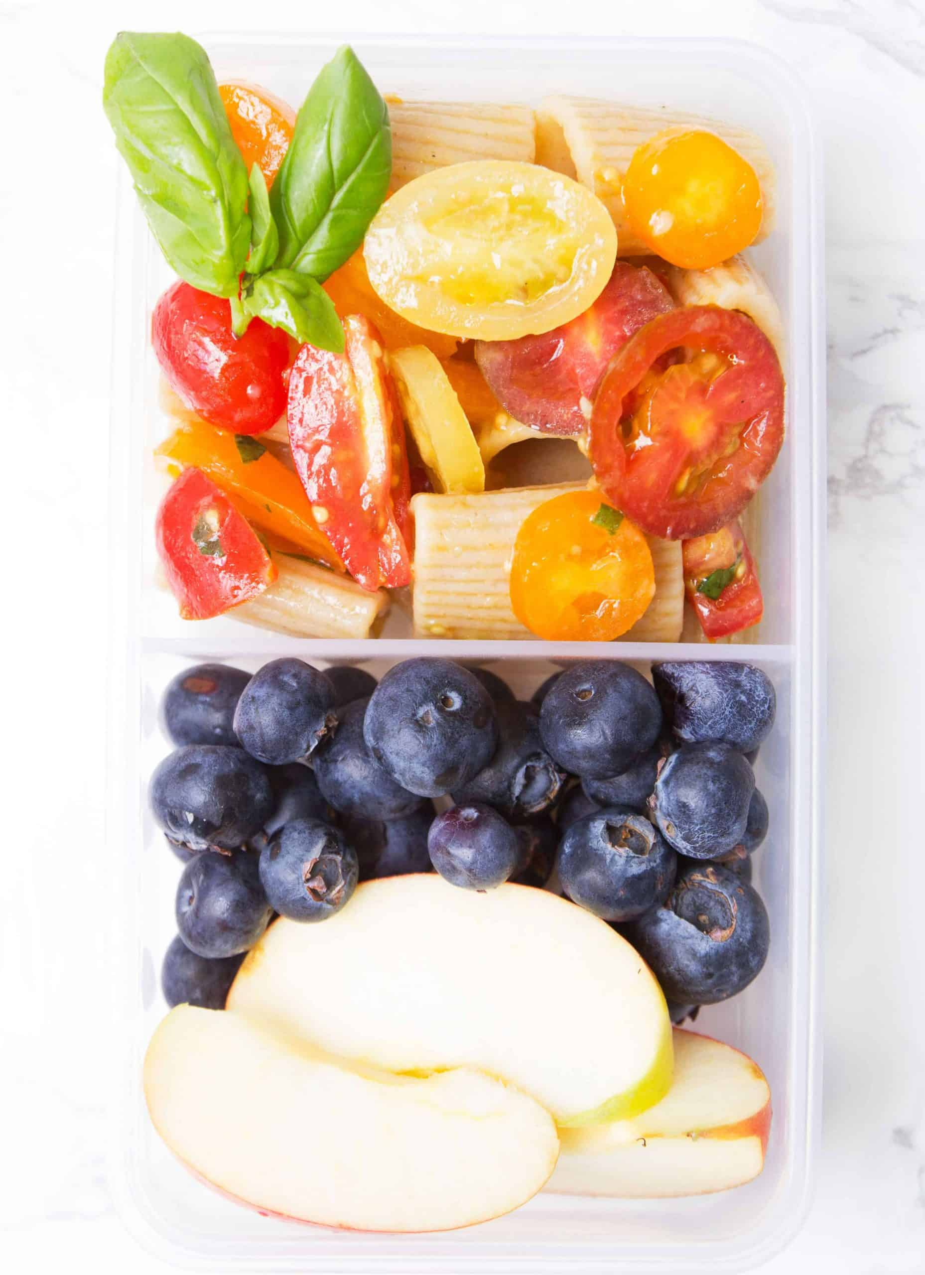 Top view of a meal prep container full of cherry tomato pasta, blueberries and apple slices - The clever meal.