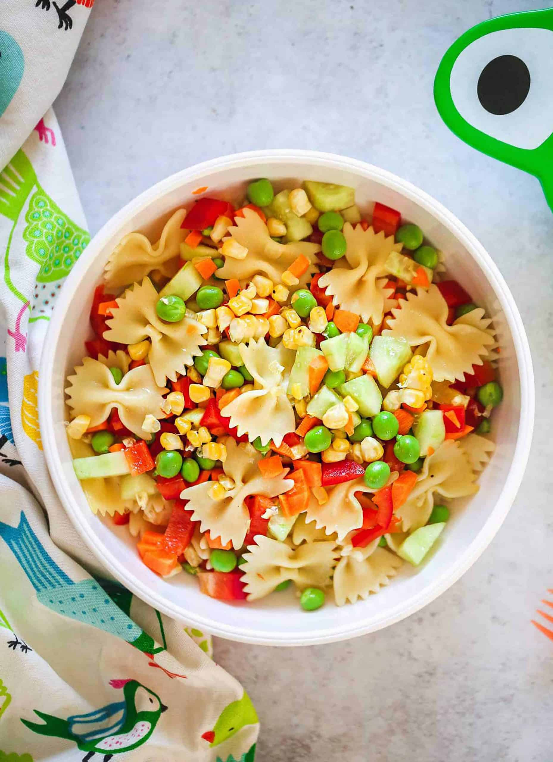 Top view of a white bowl full of pasta, peas and diced vegetables - Little Sunny Kitchen.