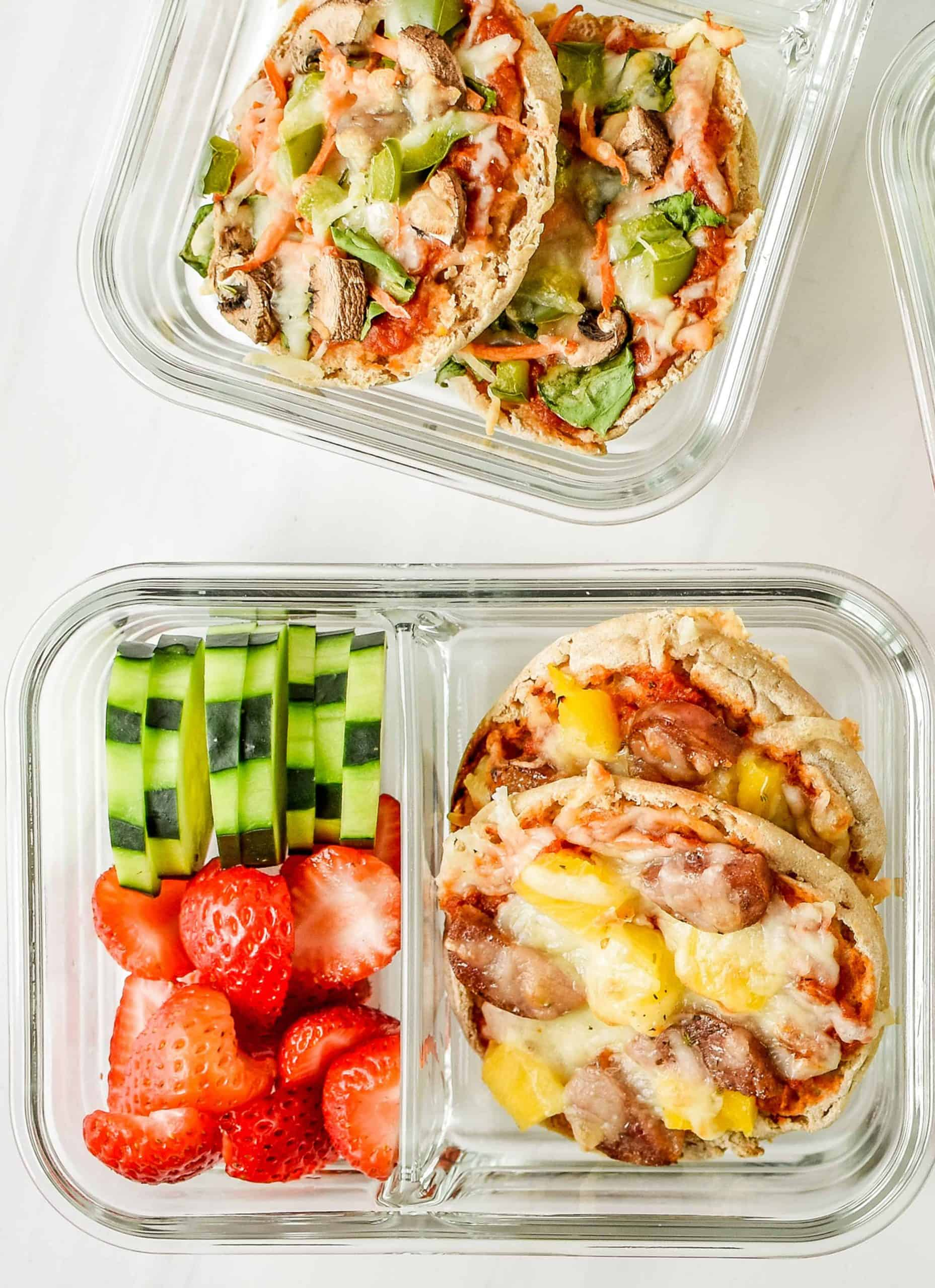 Muffins pizza in a meal prep container with slices of cucumber and strawberries - Project meal plan.