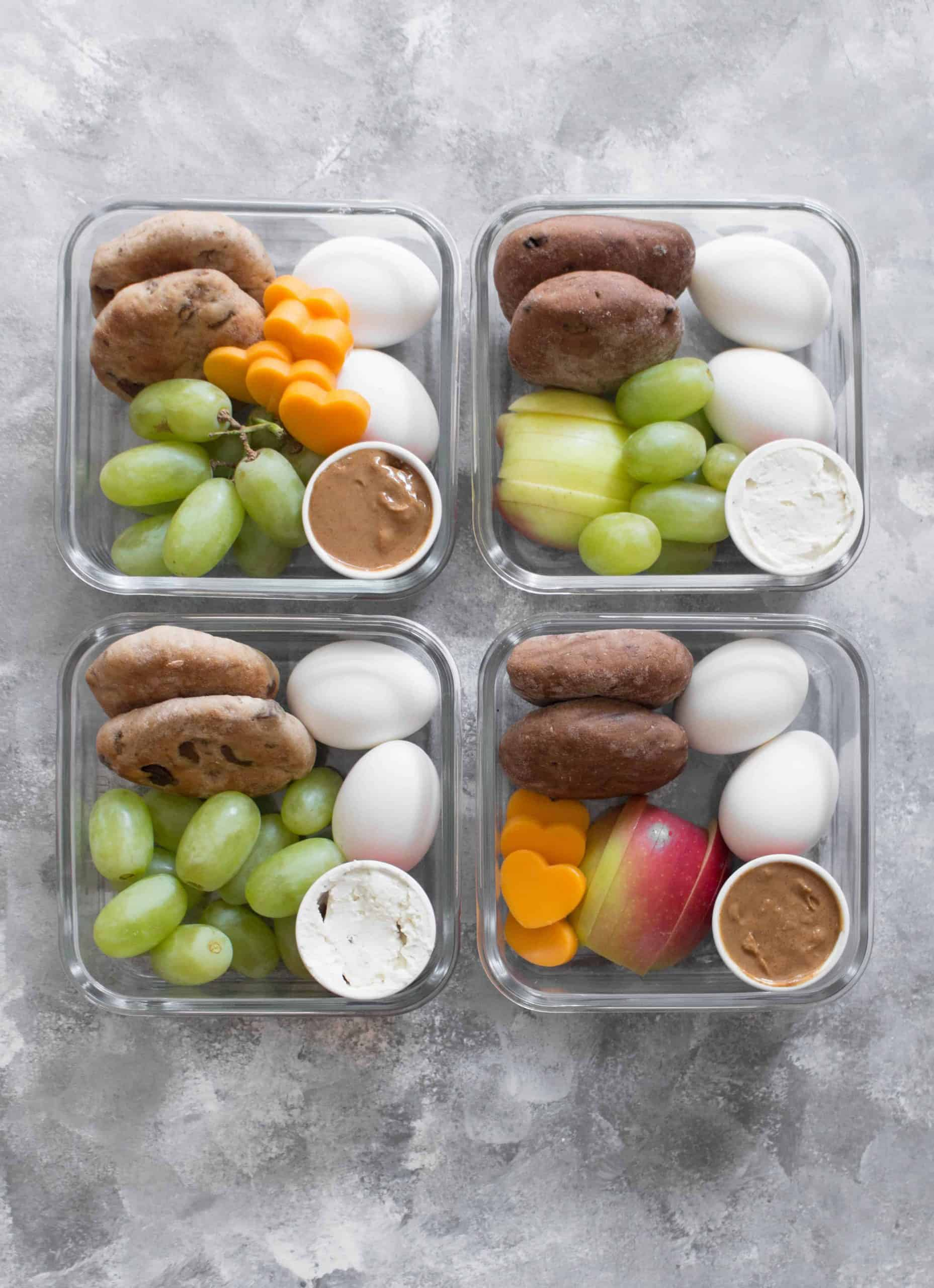 Top view of four meal prep container full of bread, boiled eggs and fruit - Recipe by Carmy.
