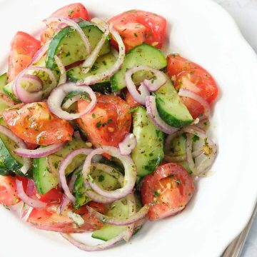Italian tomato and cucumber salad with red onion rings on a white plate.