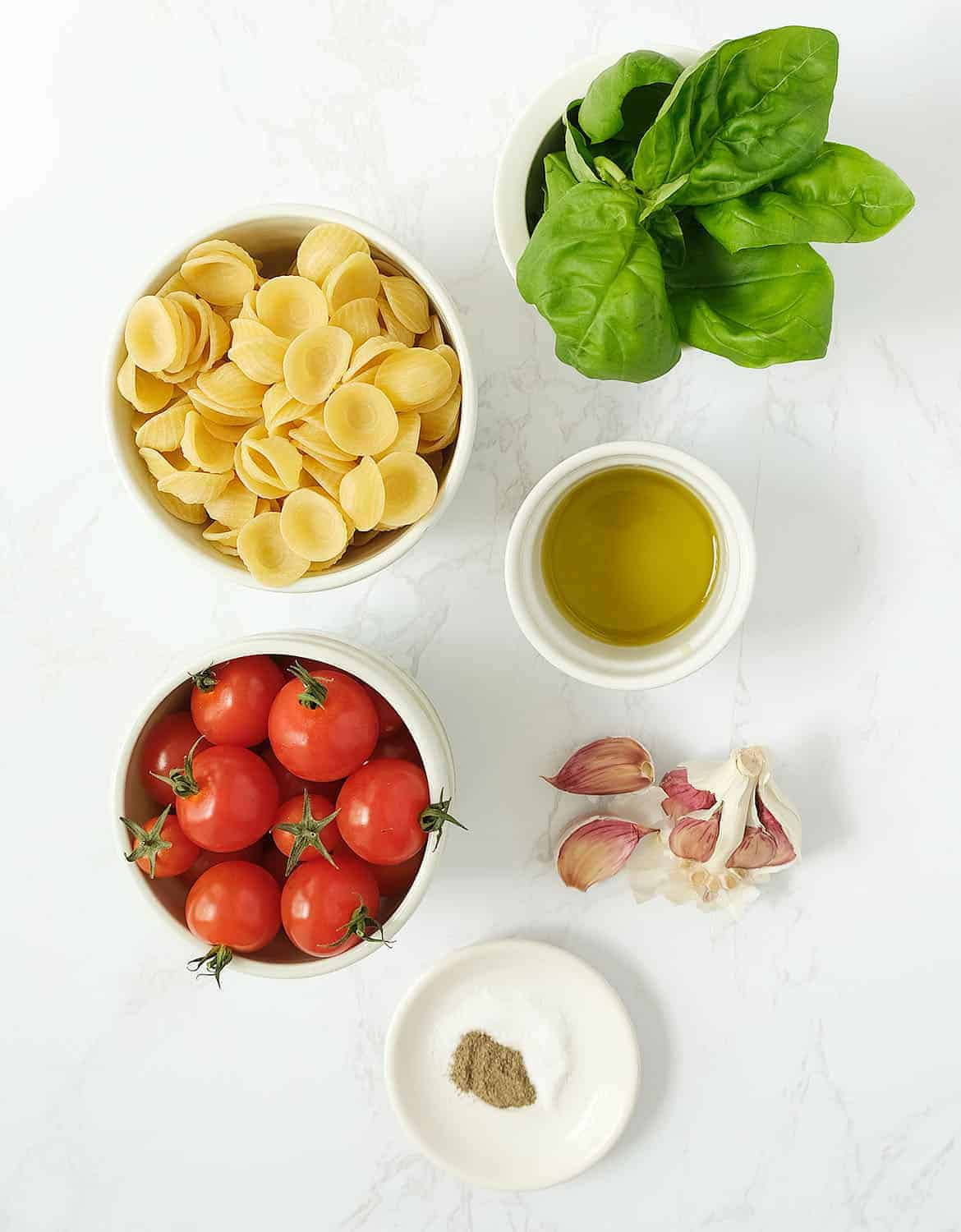 The ingredients to make this tomato pasta salad are in white bowls on a white background.