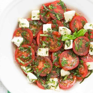 Marinated tomato and mozzarella salad with fresh herbs on a white plate.