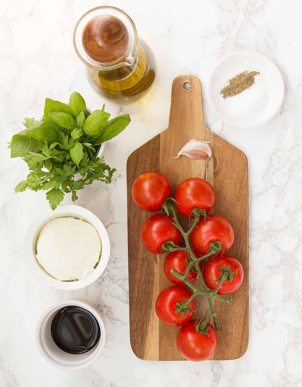 Delicious tomatoes, olive oil, balsamic vinegar and a herby and garlicky dressing for the best tomato salad ever!