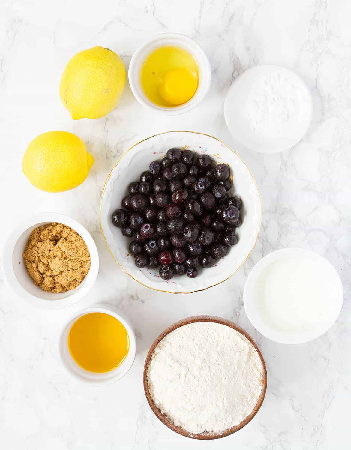 The ingredients for this blueberry muffins are arranged on a white marble surface.