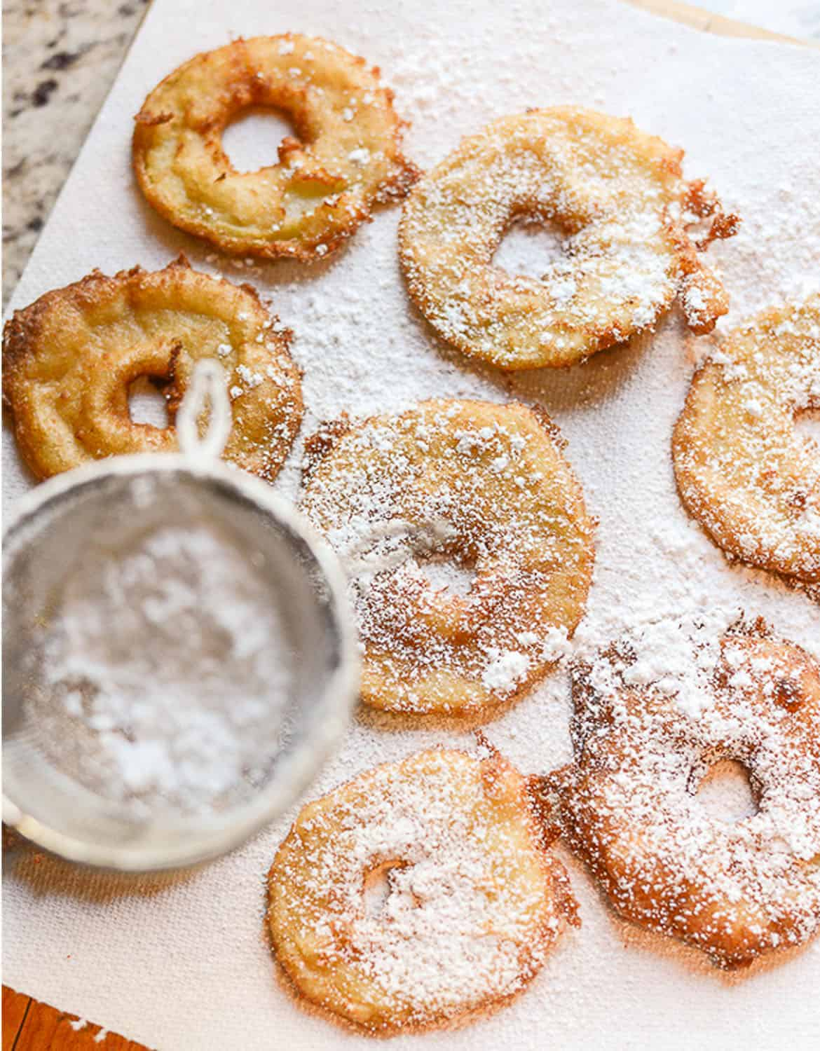 Apple fritter rings dusted with icing sugar over white parchment paper - Tikkido