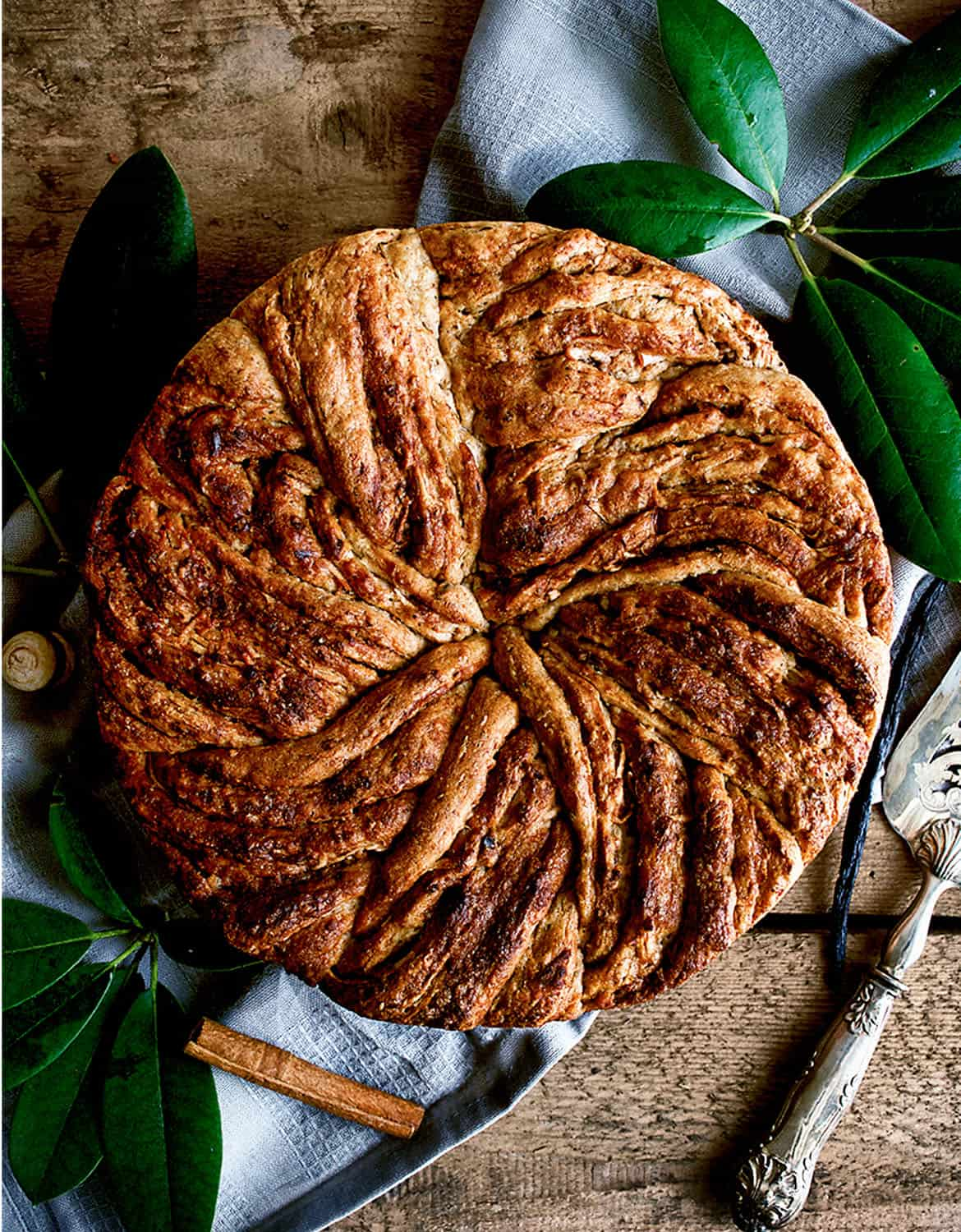 A round apple cinnamon bun cake over a rustic wooden table - Occasionally Eggs