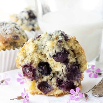 Half lemon blueberry muffin with a glass of milk in the background.