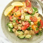 lemon couscous salad with cherry tomatoes and cucumber on a brown plate.