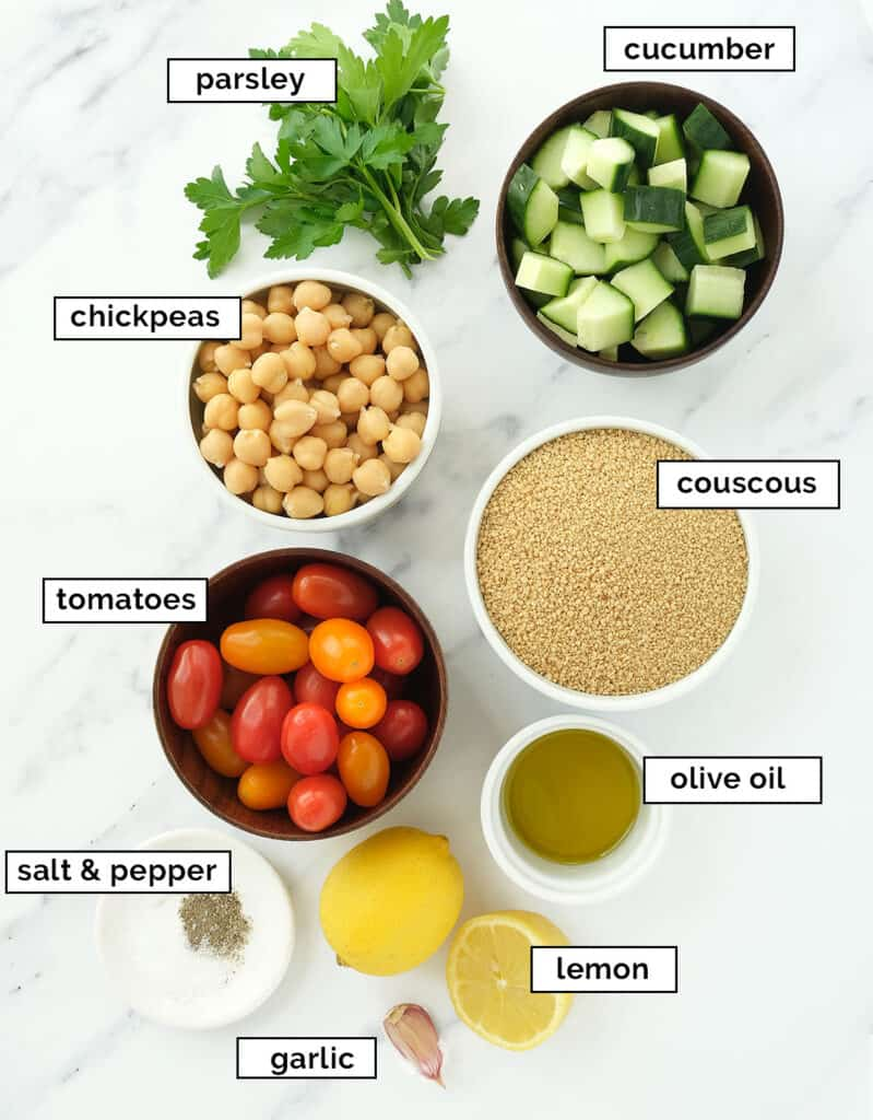 The ingredients for this lemon couscous salad are arranged over a white marble surface.