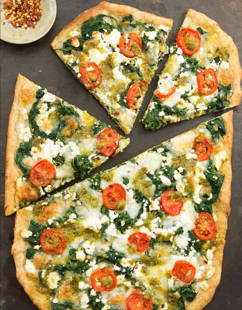 Top view of spinach pizza with feta and cherry tomatoes over a black background.