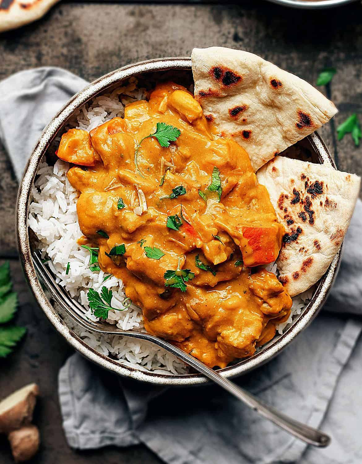 Roasted pumpkin curry in a bowl with rice and two pieces of pita bread - Full of Plants