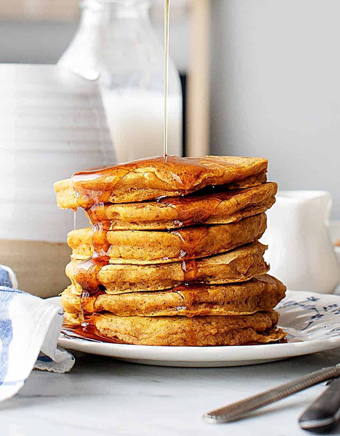 A pumpkin pancake tower with maple syrup - Love & Lemons