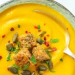 Close-up of a bowl of creamy pumpkin carrot soup garnished with croutons and chili flakes.