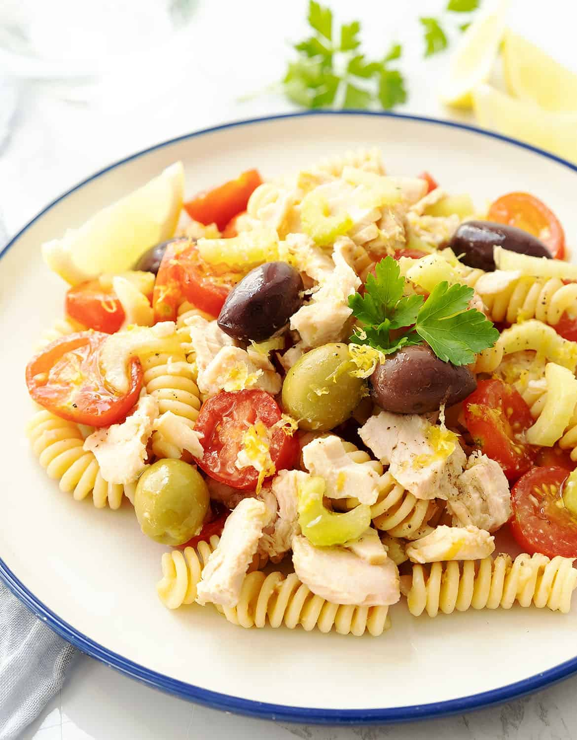 Tuna pasta salad with olive and tomatoes is served in a white plate with a blue rim.