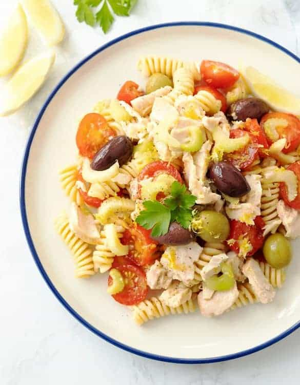 Tuna pasta salad with cherry tomatoes and olives on a white plate with a blue rim.