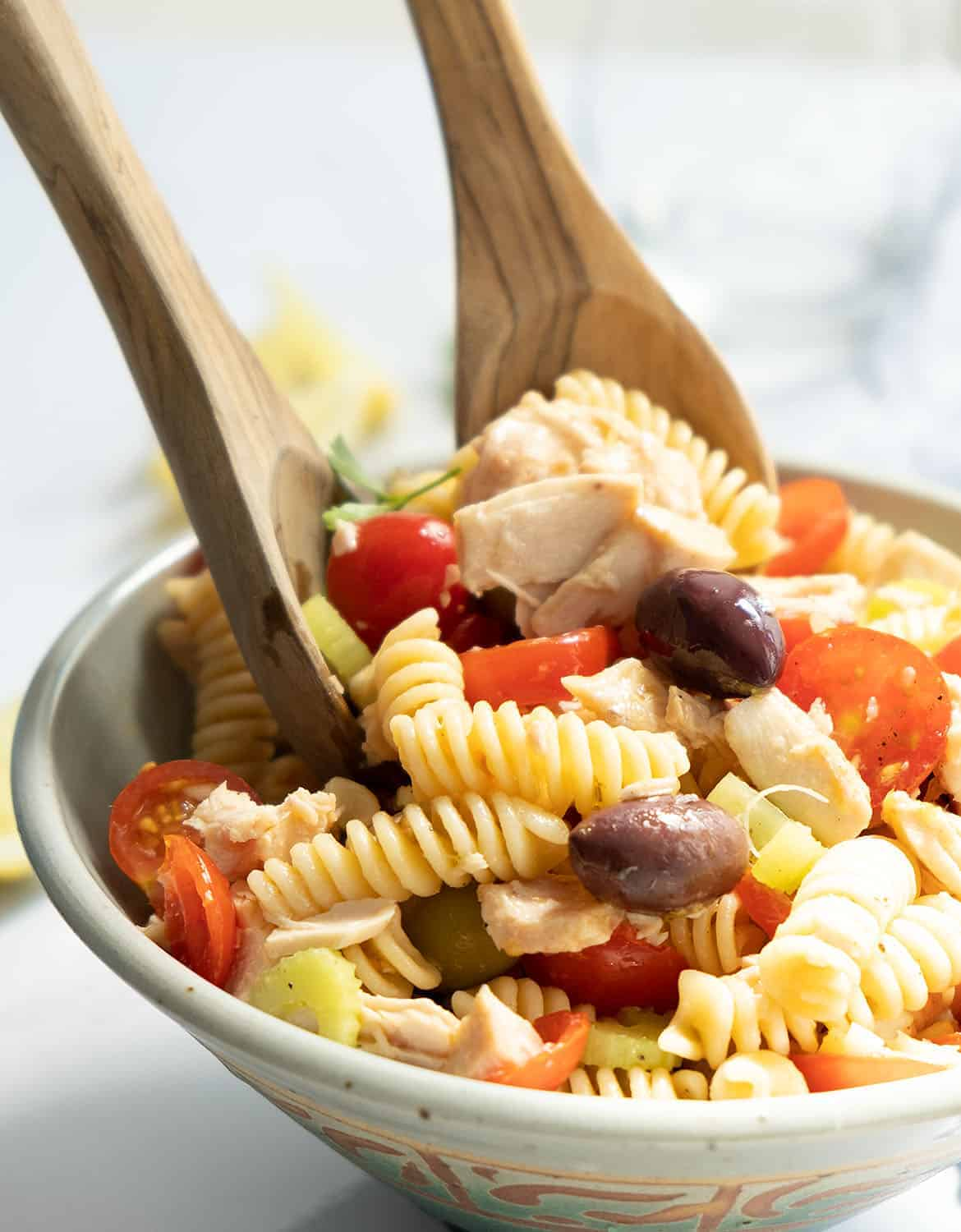 Two wooden spoons are mixing the tuna pasta salad in a bowl.