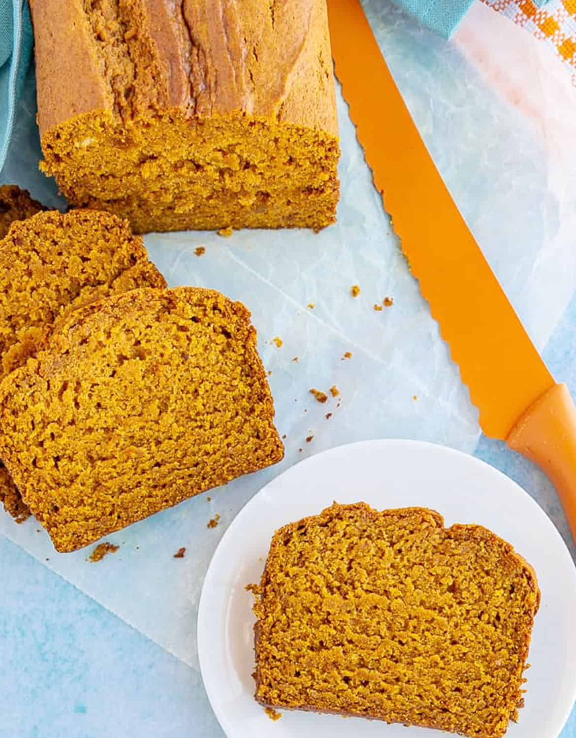 Vegan pumpkin bread cut into slices with an orange knife in the background - Love from The Oven
