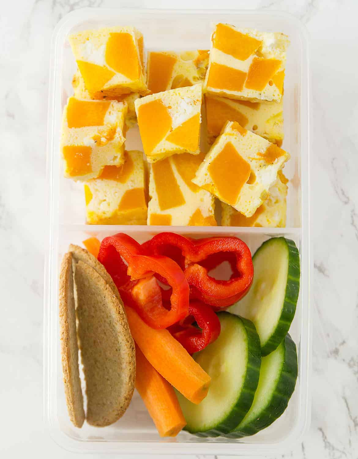 Cubed pumpkin frittata in a meal prep container with fresh vegetables on the side.