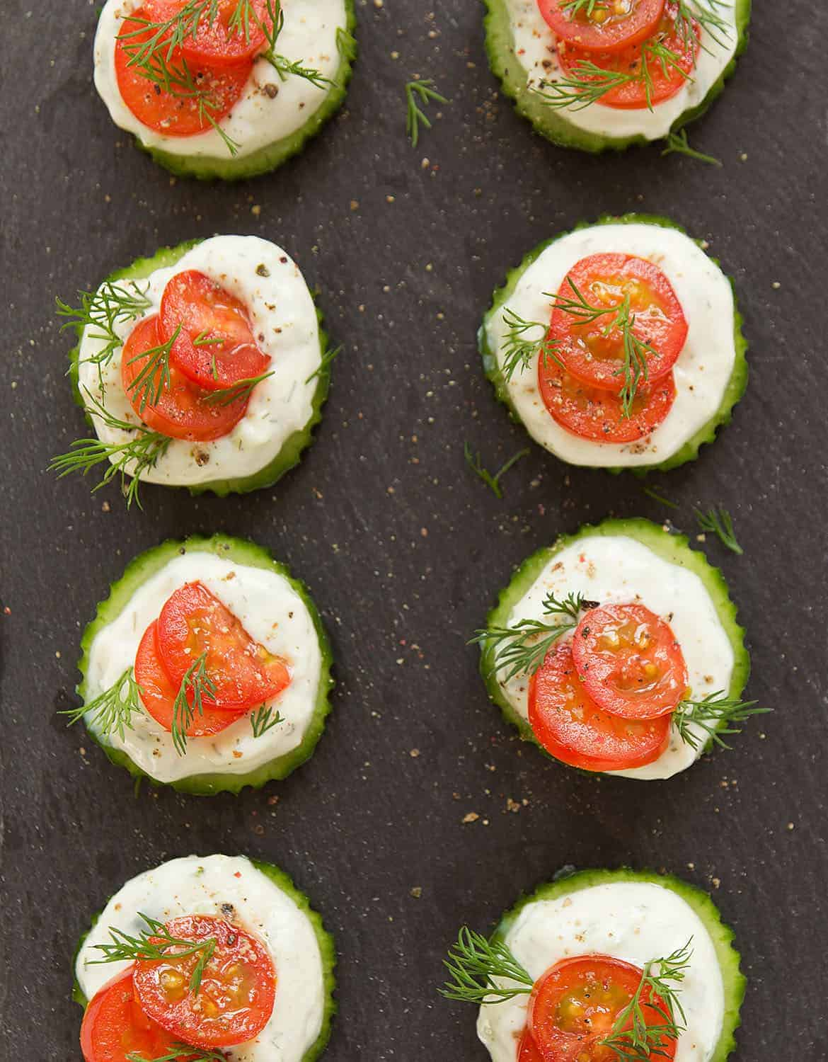 Eight slices of cucumber topped with vegan tzaziki and cherry tomatoes on a black tray - The Clever Meal