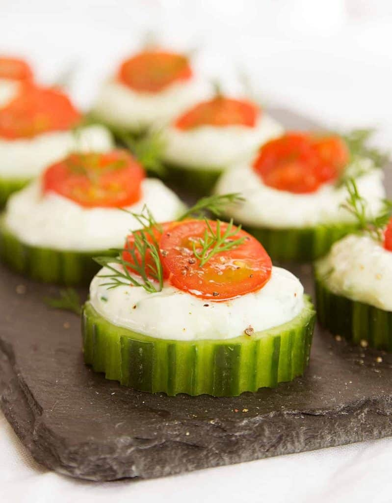Slices of cucumber topped with vegan tzatziki and cherry tomatoes served on a black tray.