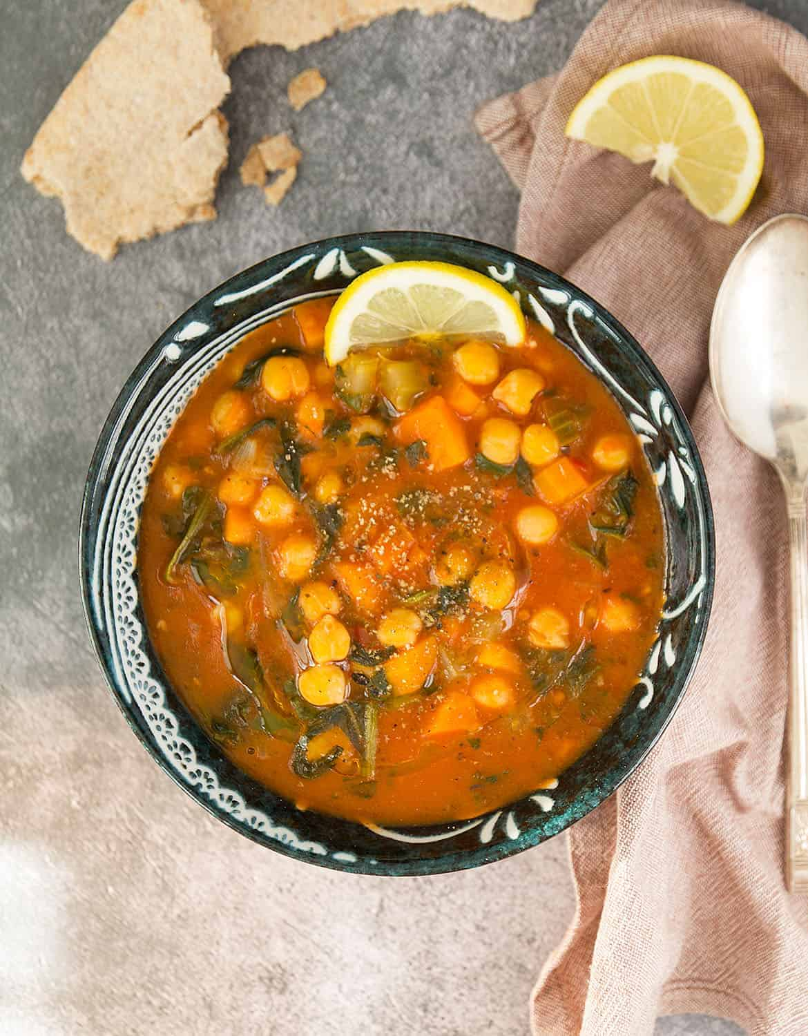 Top view of a black bowl of mediterranean chickpea soup with a slice of lemon over a grey background.