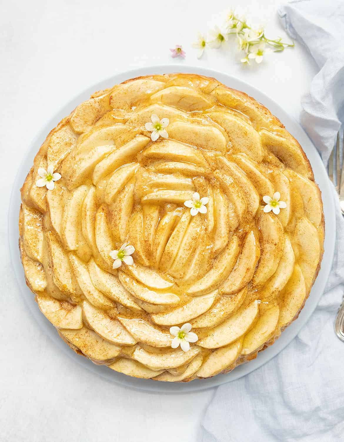 A round apple cake decorated with small flowers - The Clever Meal