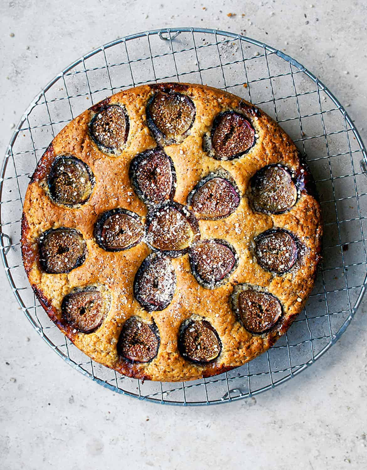A round cake with figs over a grey background - Occasionally Eggs