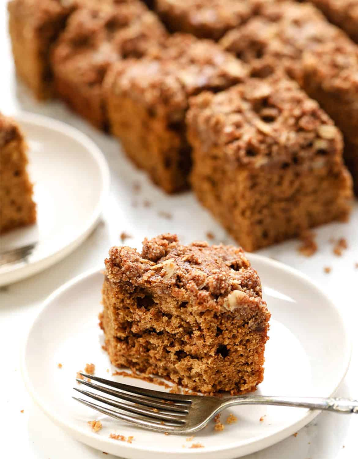 A portion of coffee cake on a white plate with a fork - Simply Quinoa