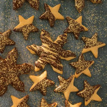 Star shaped Christmas cookies over a black background.