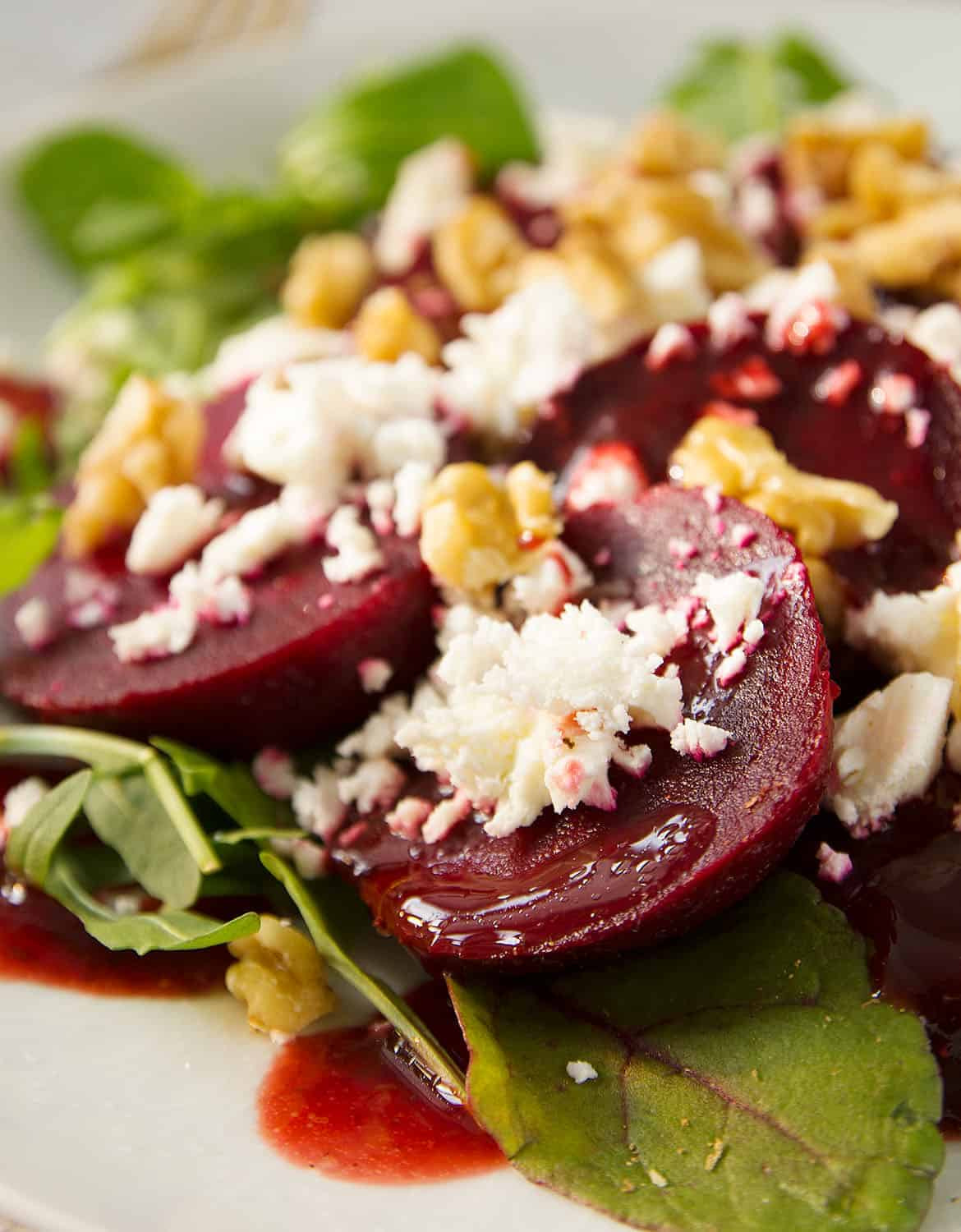 A close-up of beetroot salad with feta with a ruby dressing over a white plate.