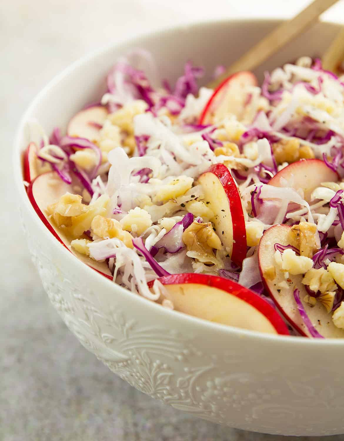 A close-up of a white bowl full of cabbage salad, apple slices and walnuts.