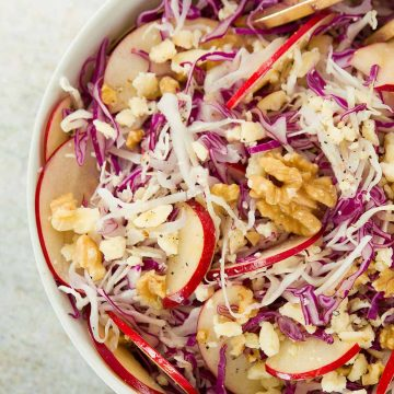 A white bowl full of cabbage salad with apple slices and walnuts.