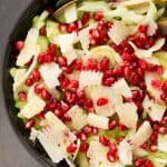 A black bowl of celery salad with parmesan and pomegranate.