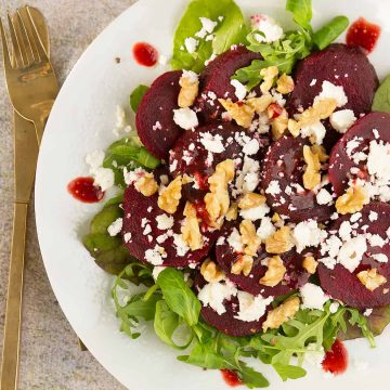 Beetroot salad with feta over a white serving plate.