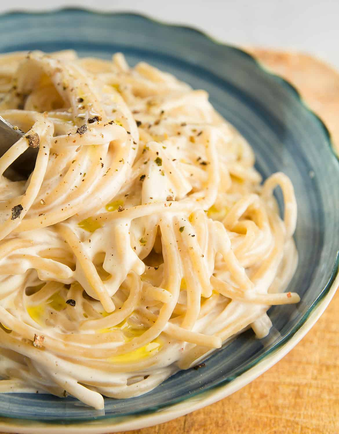 A portion of easy cream cheese pasta on a blue plate.