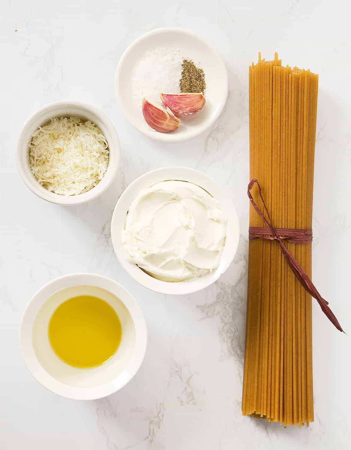 The ingredients to make this cream cheese pasta are arranged on a white table.