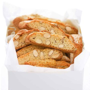 Almond biscotti on a white box over a total white background.