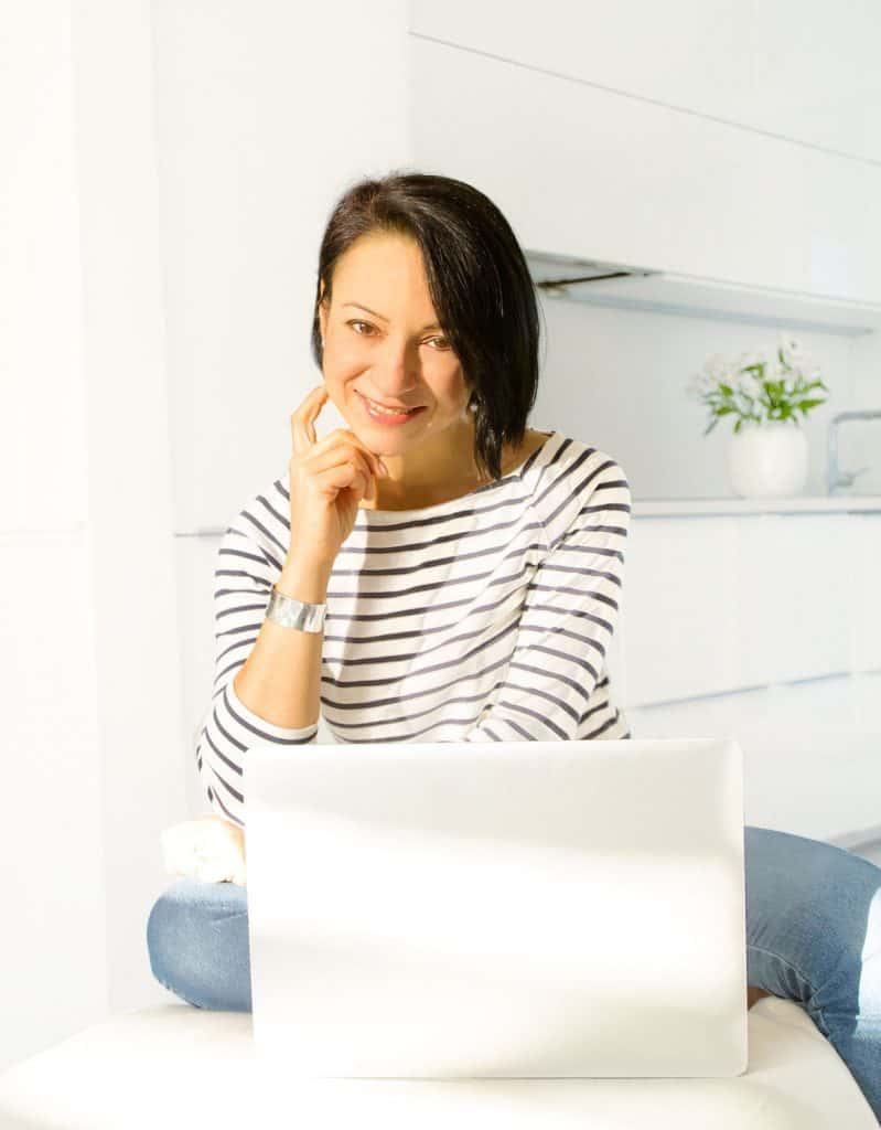 Myself smiling and wearing a stripe top and blue jeans in front of my laptop, my white kitchen in the background.