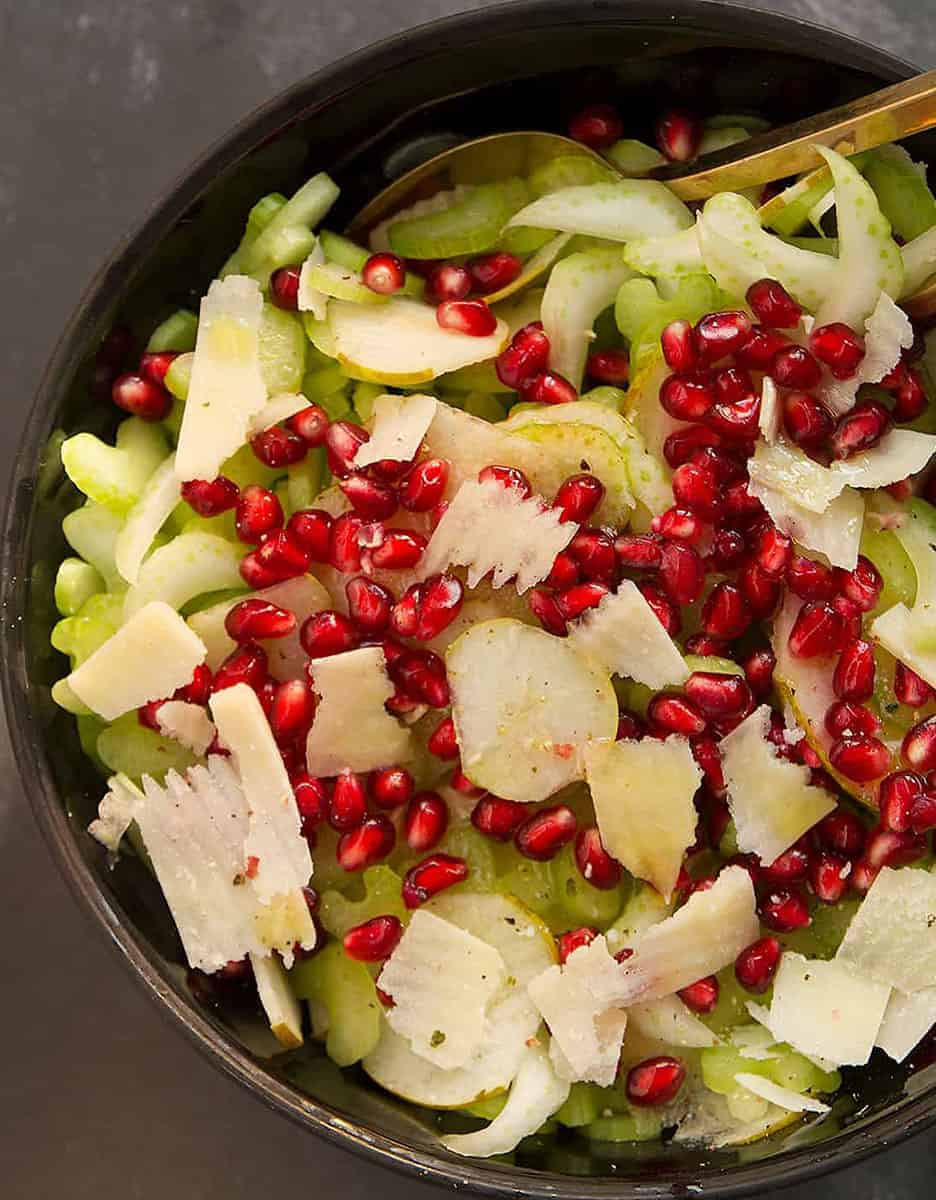 Celery salad with pomegranate and parmesan in a black salad bowl - The Clever Meal